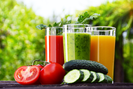 Glasses with fresh vegetable juices in the garden  Detox dietの写真素材