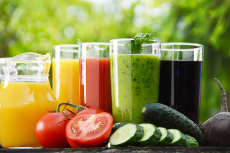 Glasses with fresh vegetable juices in the garden.