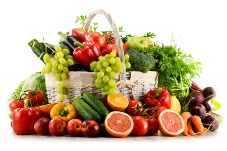 Variety of organic vegetables and fruits in wicker basket isolated on whiteの写真素材