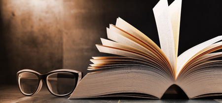 Photo pour Composition with open book and glasses on the table. - image libre de droit