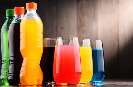 Photo pour Glasses and bottles of assorted carbonated soft drinks in variety of colors - image libre de droit