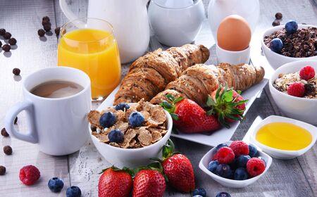 Foto de Breakfast served with coffee, orange juice, croissants, egg, cereals and fruits. Balanced diet. - Imagen libre de derechos