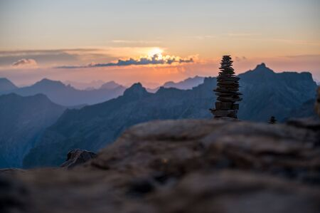 stone cairn in the Swiss Alps at sunset
