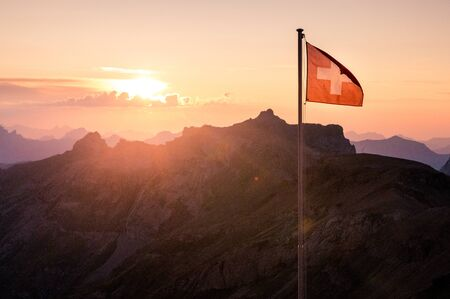 backlit swiss flag at sunset in the Swiss Alps