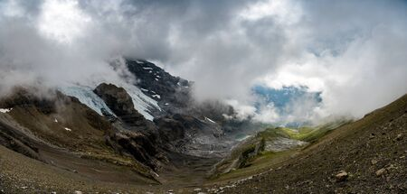 landscape at HohtÌrli with Oeschinensee in the distance in misty clouds while hiking