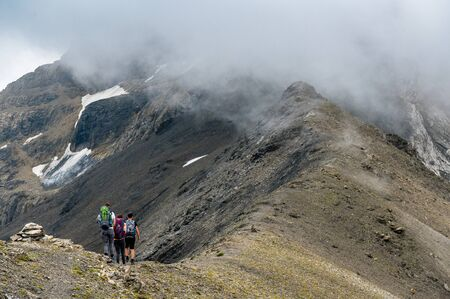 group of three alpine hikers on a ridge in the Bernese Alps