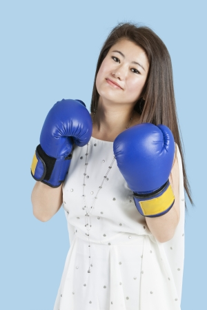 Portrait of a beautiful young woman wearing boxing gloves over blue background