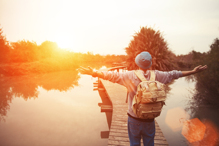 happy traveler on the lake with outspread hands looking at sunset