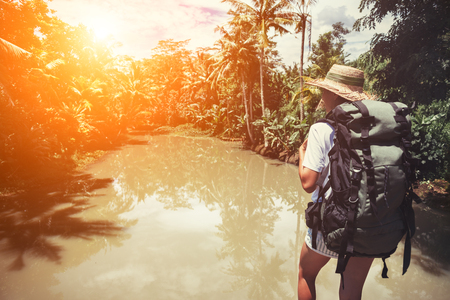 Traveling woman with backpack and straw hat near tropical river, intentional sun glare