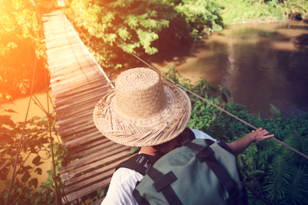 Woman with backpack and hat traveling across danger hanging bridge, intentional sun glare