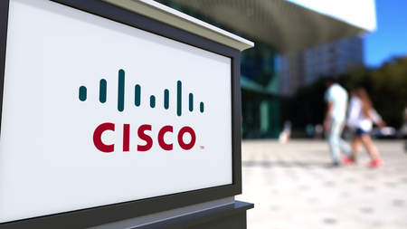 Street signage board with Cisco Systems logo. Blurred office center and walking people background. Editorial 3D rendering United States