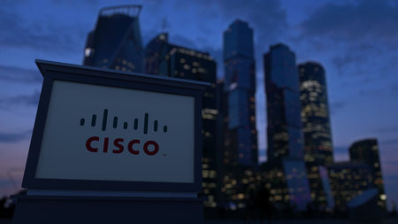 Street signage board with Cisco Systems logo in the evening. Blurred business district skyscrapers background. Editorial 3D United States