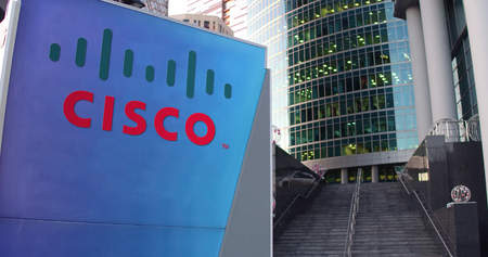 Street signage board with Cisco Systems logo. Modern office center skyscraper and stairs background. Editorial 3D rendering United States