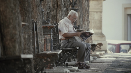 VALENCIA, SPAIN - SEPTEMBER 22, 2018. Elder man sitting on park bench and reading newspaper