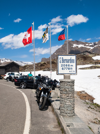 San Bernardino pass, Switzerland - May 14, 2015: Motorcycle parked near to each pass. This point is the top of the pass and many tourists taking pictures suggestive.