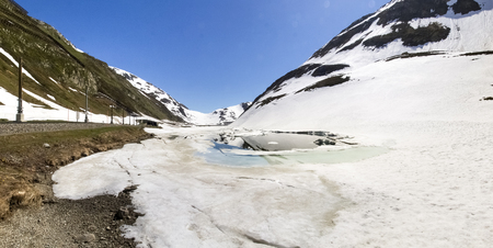 Oberalp pass, Switzerland : Artificial lake ice. The lake is illuminated by the sun during a beautiful day on the day of the Feast of the Ascension