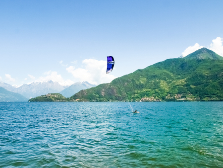 Pianello del Lario, Italy - May 16, 2015: Kitesurfing action at the lake. Preparation, starting from the beach, sailing in the lake.