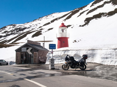 Andermatt, Switzerland - May 14, 2015: Lighthouse Oberalppass. The lighthouse is surrounded by snow and is illuminated by the sun during a beautiful day on the day of the Feast of the Ascension