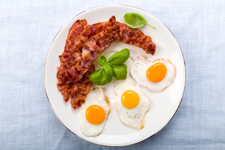 Bacon and quail eggs with basil