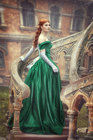 Beautiful, young, red-haired girl in a green medieval dress, climbs the stairs to the castle. Fantastic photosession.