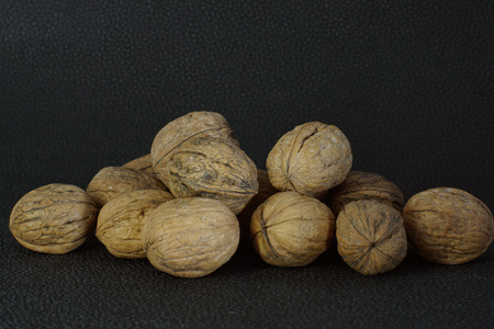 Walnuts in shell are stacked on a dark background
