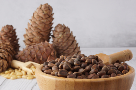 Uncleaned pine nuts in a bowl with a wooden spatula, cedar cones on a wooden table.