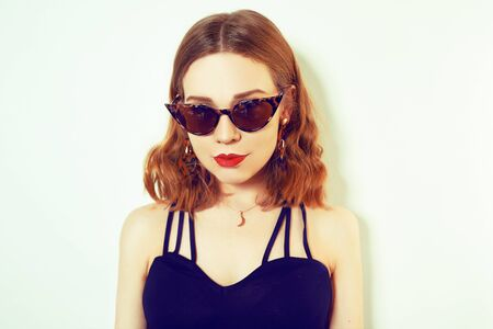 Photo pour Hipster girl whole in a black dress, on a white background. Girl in unusual sunglasses and earrings. Fashion girl with a short haircut. - image libre de droit