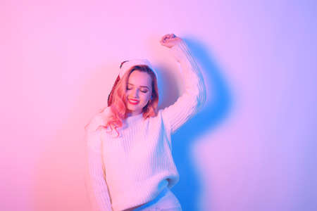 Photo for Girl in a white sweater and santa hat in neon light. Woman with professional makeup and red lips. Model with pink hair dancing. New Year Christmas. - Royalty Free Image
