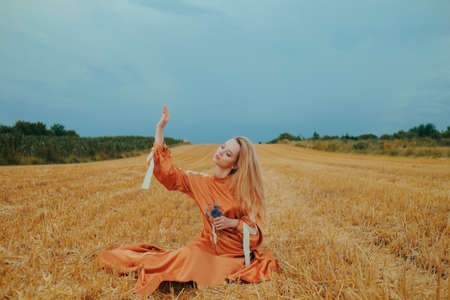 Photo pour A beautiful girl in a dress sits on a wheat field. Fabulous photo of a blonde outside the city. A woman without allergies holds blue flowers. - image libre de droit
