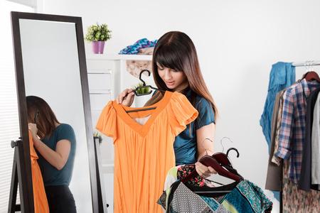Foto de Beautiful young woman near rack with clothes making chioce - Imagen libre de derechos
