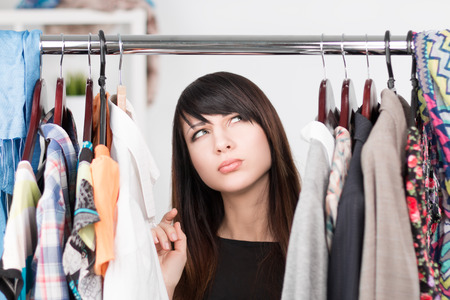 Beautiful young confused woman near rack with clothes. Nothing to wear concept