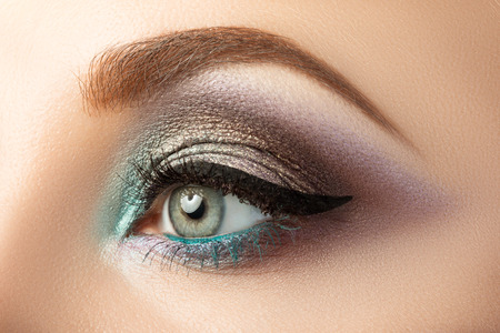 Photo pour Close-up of woman's eye with creative modern make-up. Smoky eyes and arrow. - image libre de droit