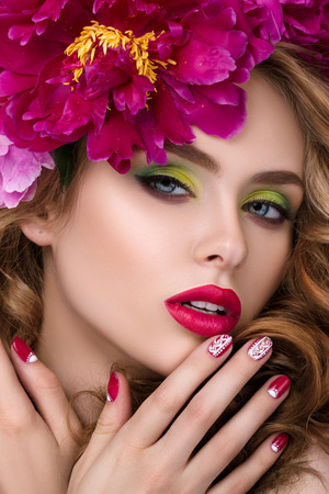 Close-up beauty portrait of young pretty girl with flower wreath in her hair wearing bright pink lipstick and touching her lips.