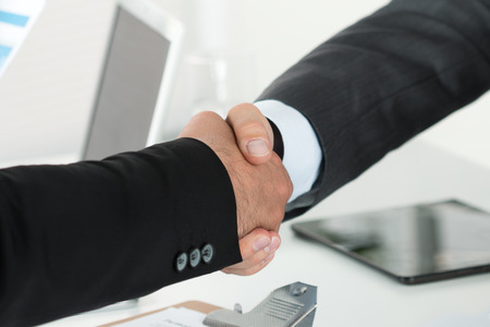 Photo for Business handshake. Two businessman shaking hands with each other in the office. - Royalty Free Image