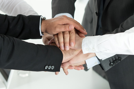 Foto de Closeup of business team showing unity with putting their hands together on top of each other. Concept of teamwork. - Imagen libre de derechos