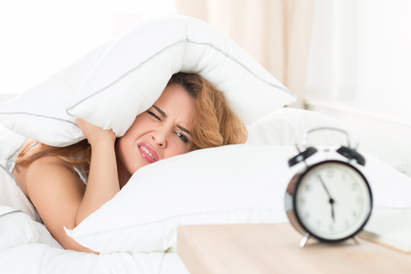 Young beautiful woman hates waking up early in the morning. Sleepy girl looking at alarm clock and trying to hide under the pillow