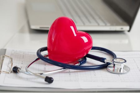 Read heart and stethoscope laying on cardiogram chart at doctor's working table closeup. Medical help, prophylaxis, disease prevention or insurance concept.