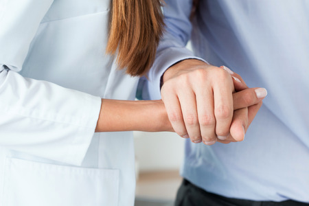 Female medicine doctor helping her patient to walk after operation by supporting his hand. Hands close-up. Rehabilitation, kindness, healthcare and medicine concept