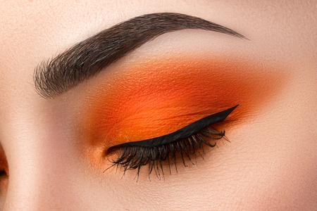 Close-up of woman eye with beautiful orange smokey eyes with black arrow makeup. Modern fashion make-up.