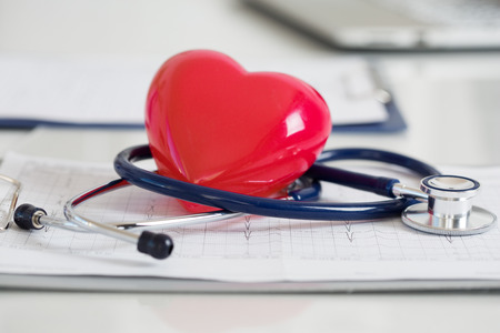 Photo pour Stethescope and red heart lying on cardiogram. Healthcare, cardiology and mediacal concept - image libre de droit