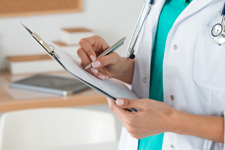 Photo for Close-up view of female doctor hands filling patient registration form. Healthcare and medical concept - Royalty Free Image