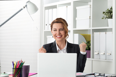 Photo for Portrait of happy young successful businesswoman celebrate something with arms up. Happy woman sit at office and look at laptop. Positive emotion. Big deal, promotion, lottery win or discount concept - Royalty Free Image