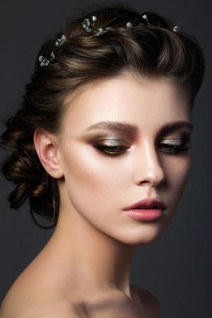 Foto de Portrait of young beautiful woman with bridal makeup and coiffure. Modern smokey eyes make up. Studio shot. Salon make-up - Imagen libre de derechos