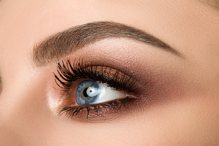 Close up of blue woman eye with beautiful brown with red and orange shades smokey eyes makeup. Modern fashion make up.