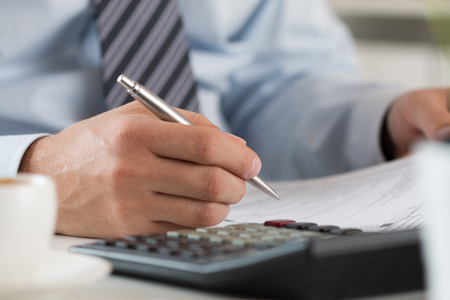 Photo pour Close up of male accountant making calculations. Man writing something sitting at his office. Partnership agreement, contact signing, closing balance, making financial report or economy concept - image libre de droit
