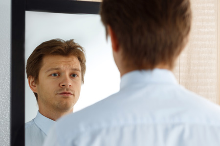 Foto de Portrait of unsure young businessman with unhappy face looking at the mirror. Man preparing for important meeting, new job interview or dating. Difficult relationship, stress management concept - Imagen libre de derechos