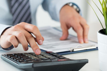 Close up of male accountant or banker calculating or checking balance. Bookkeeper or financial inspector making financial report. Home finances, investment, economy, saving money or insurance concept