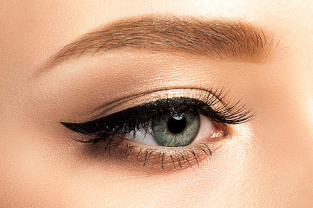 Foto de Close up view of gray woman eye with beautiful golden shades and black eyeliner makeup. Classic make up. Studio shot - Imagen libre de derechos