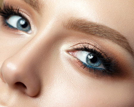 Photo pour Close up view of blue woman eye with beautiful golden shades and black eyeliner makeup. Classic make up. Perfect brows. Studio shot - image libre de droit