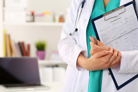 Foto de Close up view of female doctor hands holding clipping pad with patient registration form. Healthcare and medical service concept. - Imagen libre de derechos